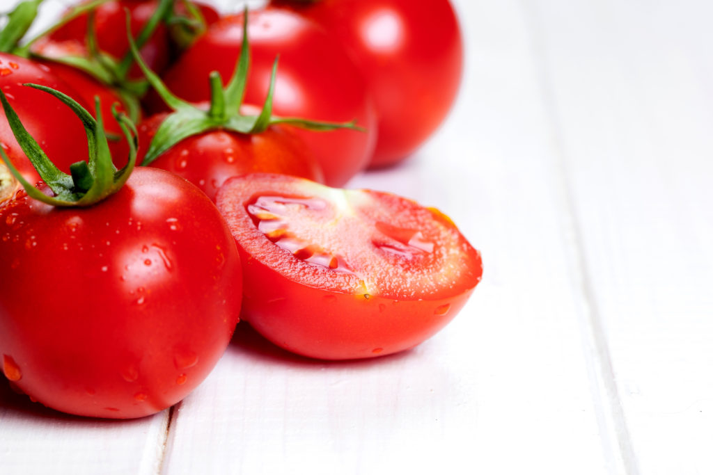 red tomatoes on wooden table